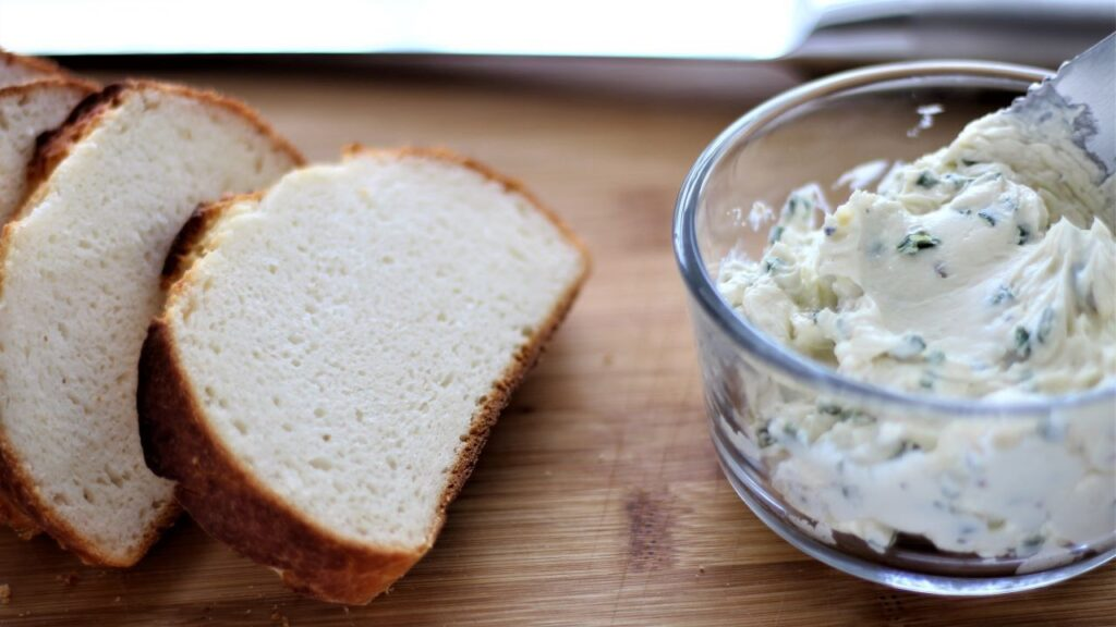 chive butter spread on cutting board with sliced bread