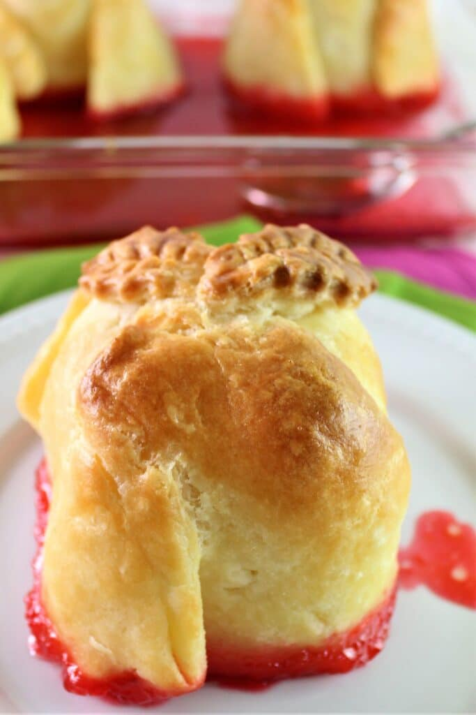 apple dumpling on white plate with red sauce underneath
