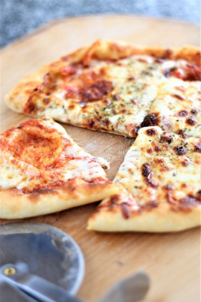 gluten free pizza on wooden pizza peel with pizza cutter