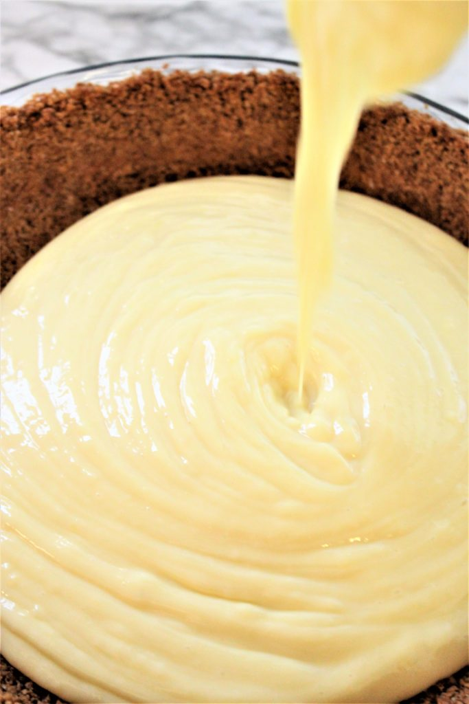 pouring filling into crust for lemon cream pie