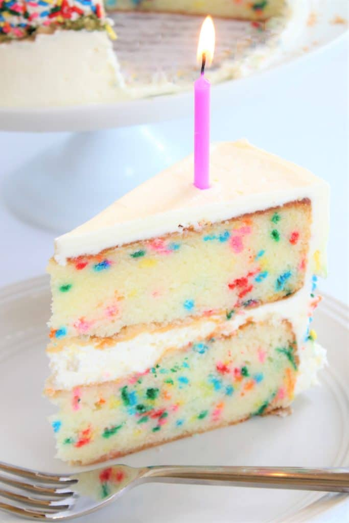 slice of funfetti cake with a candle