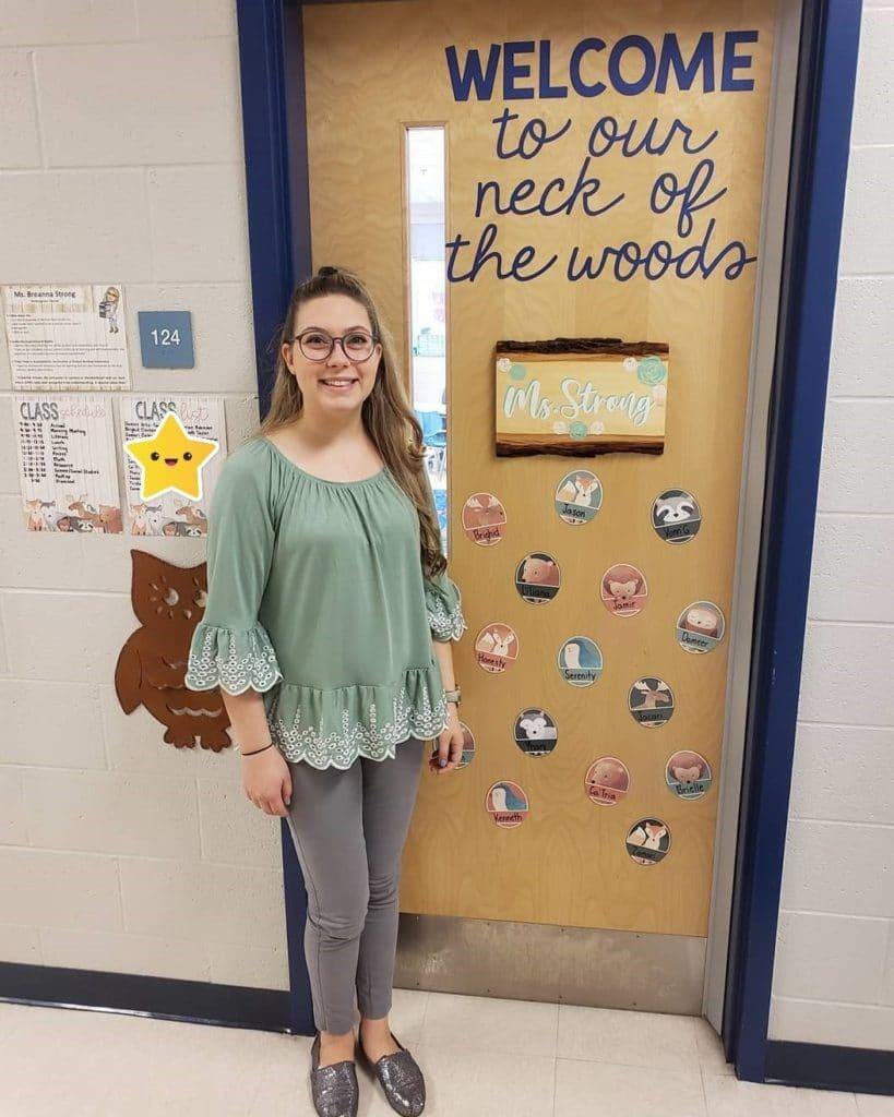 Breanna standing in front of her classroom door