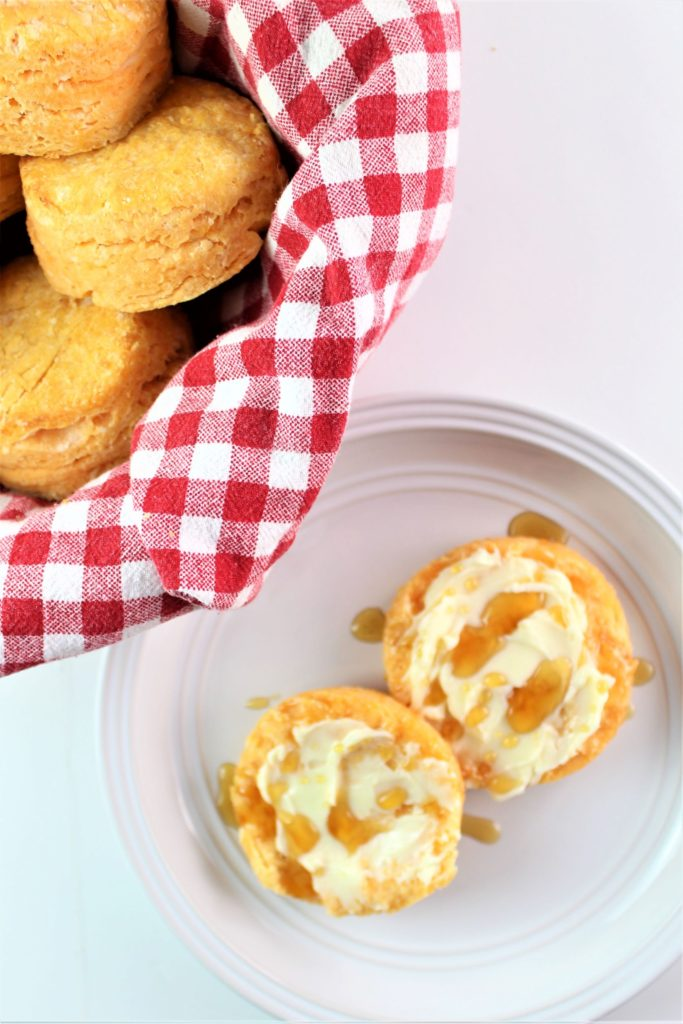 gluten free sweet potato biscuit split open and spread with butter and honey