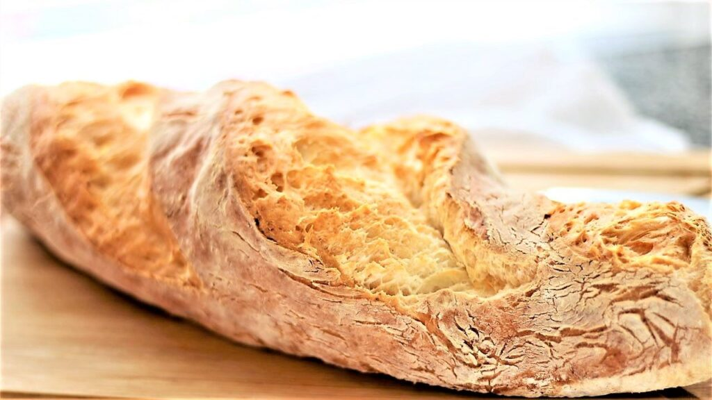 landscape view of whole baguette on cutting board