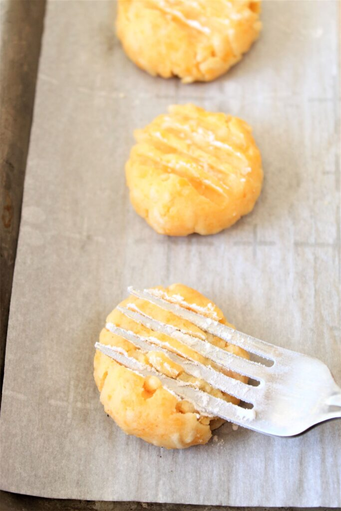 flattening cheese wafers with a fork dipped in flour