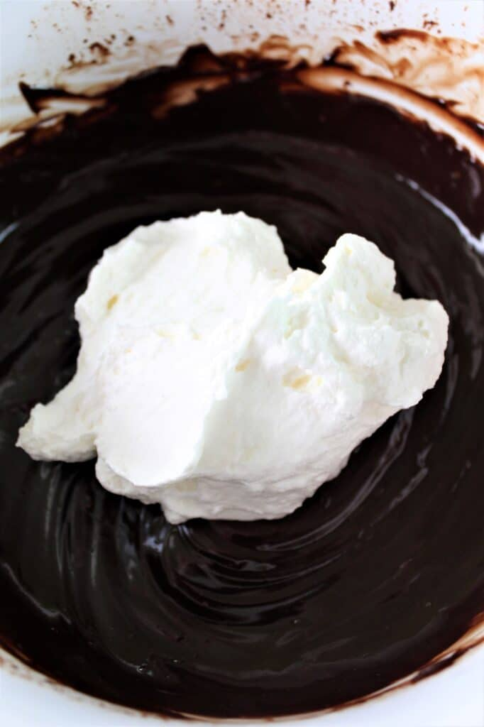 adding a little whipped cream into chocolate mixture