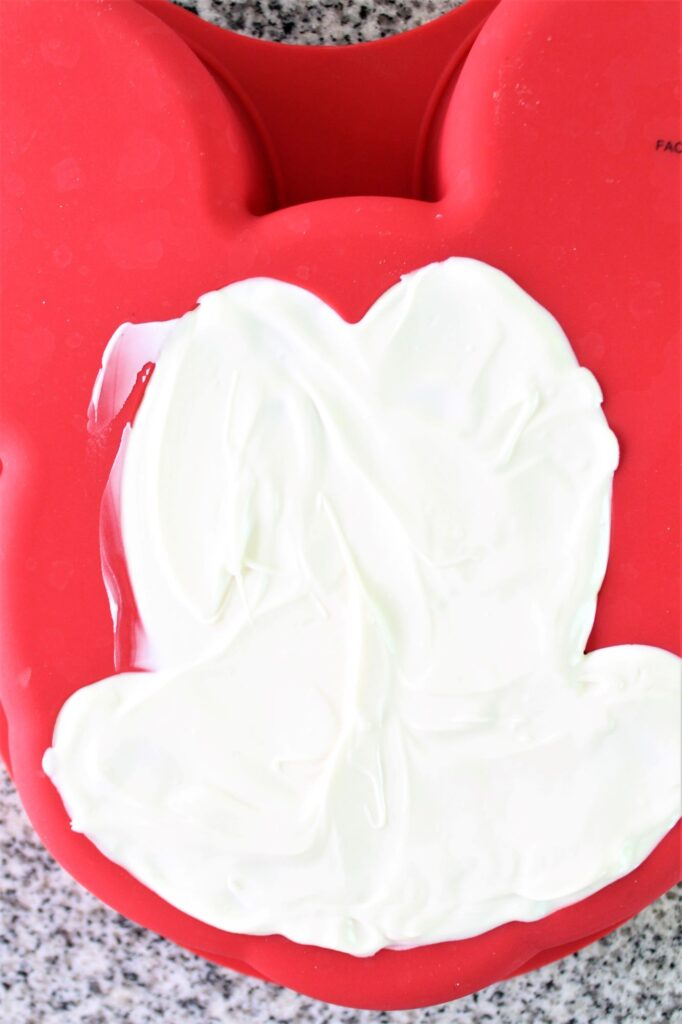 white chocolate spread onto mickey face of silicone cake mold