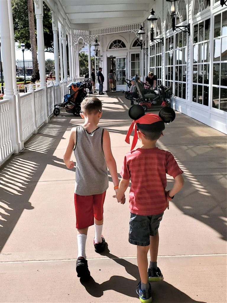 chase and wyatt holding hands while heading to breakfast at grand floridian cafe