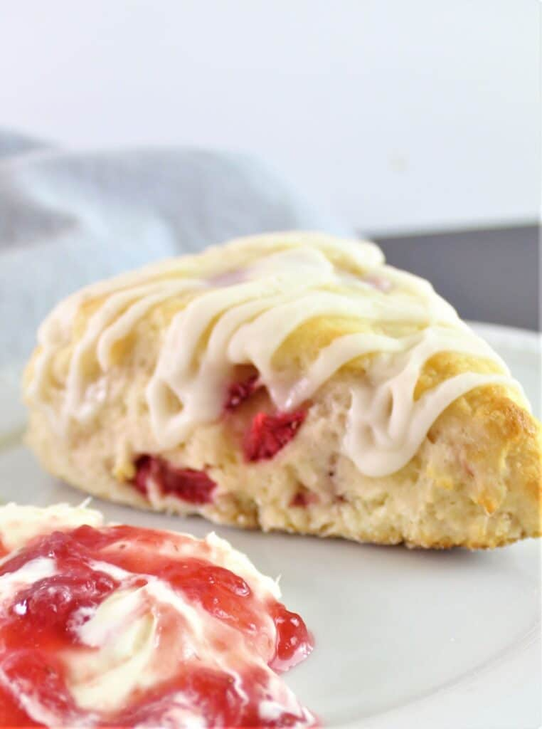 gluten free strawberry scone on plate with clotted cream and jam