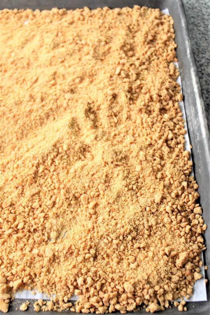 graham cracker crumbs on parchment-lined baking sheet