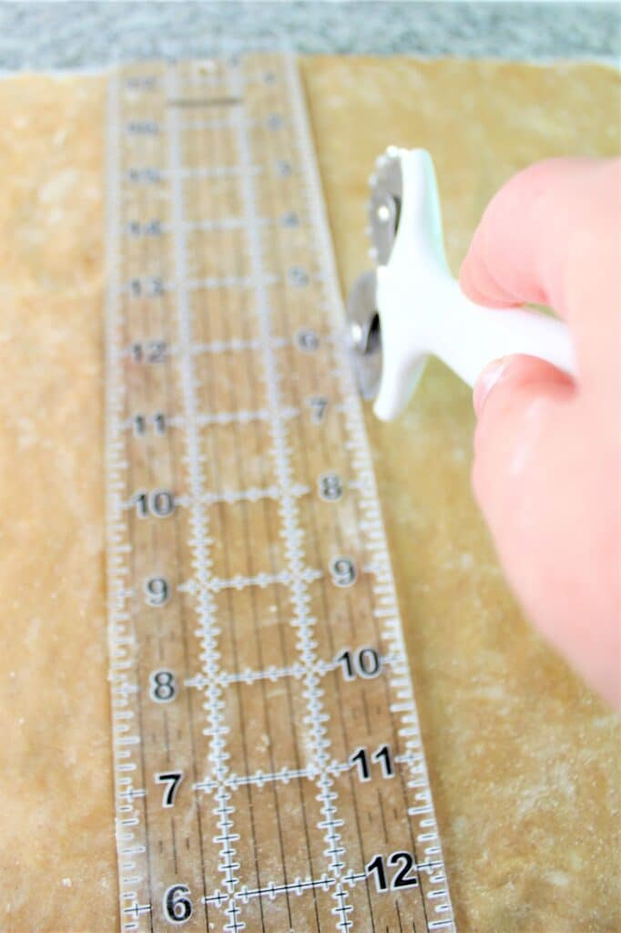 using a ruler and pastry wheel to score graham crackers