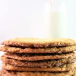 gluten free toffee cookies stacked in front of a glass of milk