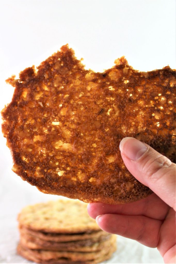 crispy cookie held up in hand with bites taken out of it