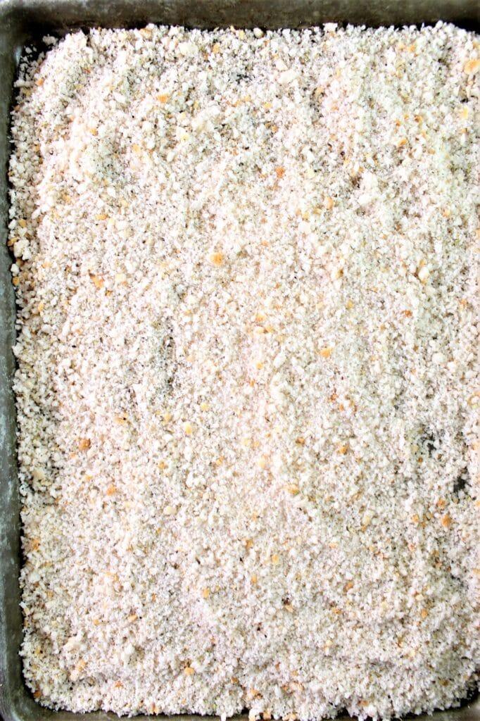 breadcrumbs spread in even layer onto baking sheet