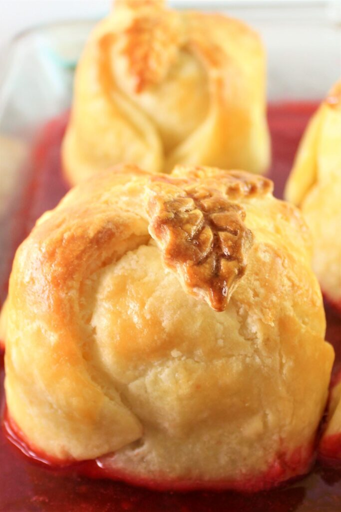 apple dumplings in glass baking dish sitting in a bright red sauce