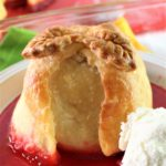 gluten free apple dumplings with vanilla ice and a pool of red cinnamon sauce