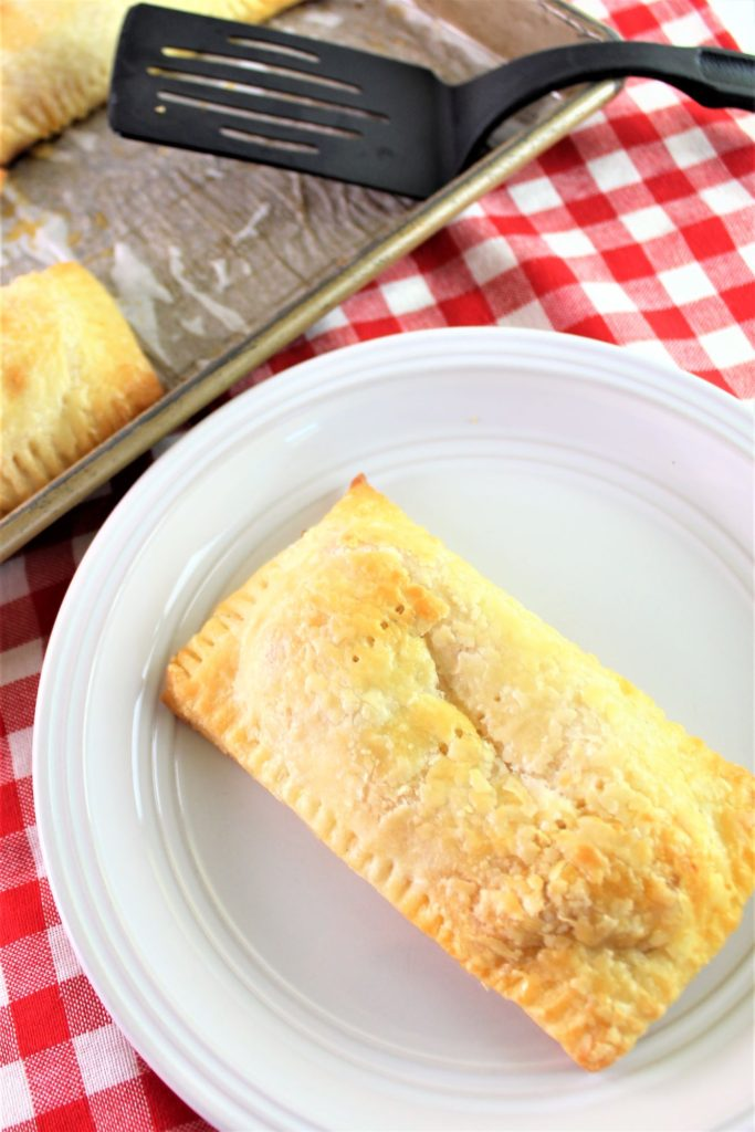 whole baked pizza hot pocket on white plate with red checked napkin in background