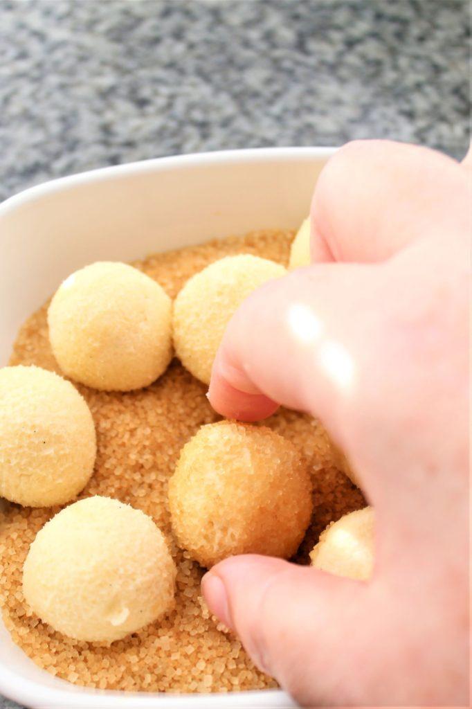rolling balls of dough in turbinado sugar