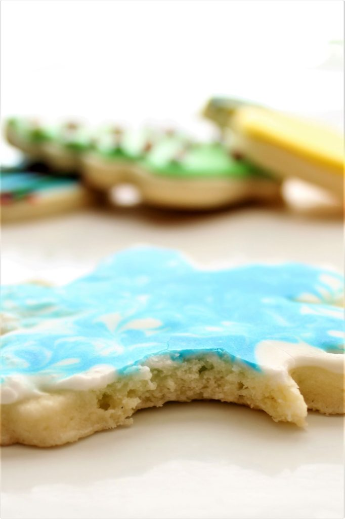blue and white cutout sugar cookie snowflake with bite taken