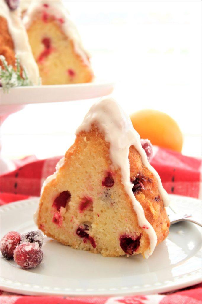 slice of gluten free cranberry orange bundt cake on white plate over red checked napkin