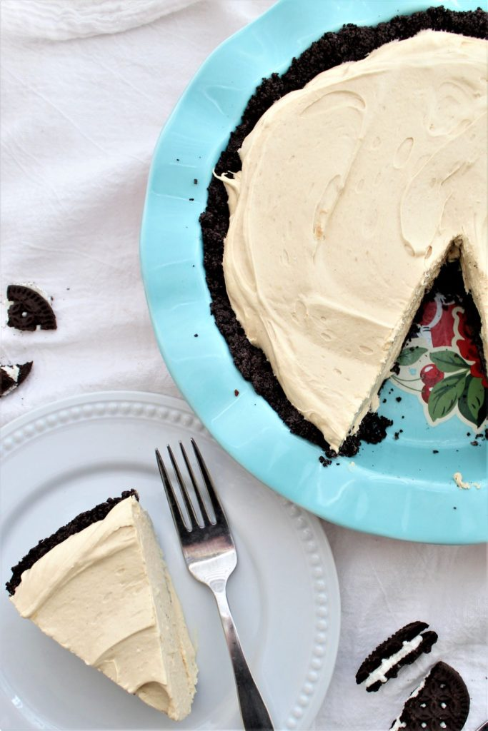 slice of pie on white plate with whole pie in blue pie pan