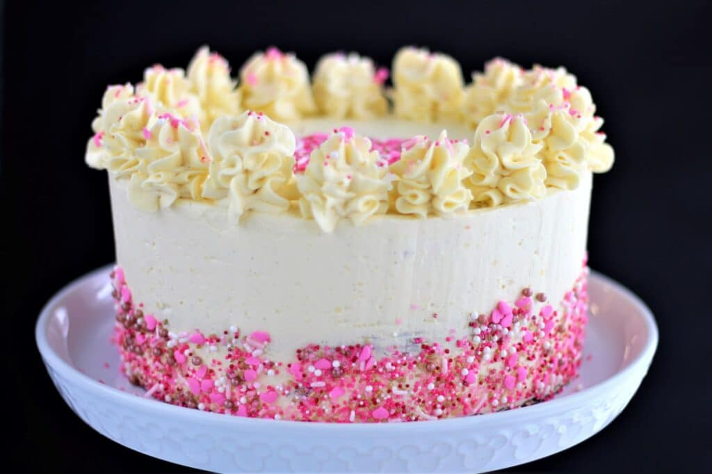 whole gluten free red velvet cake with sprinkles and black background
