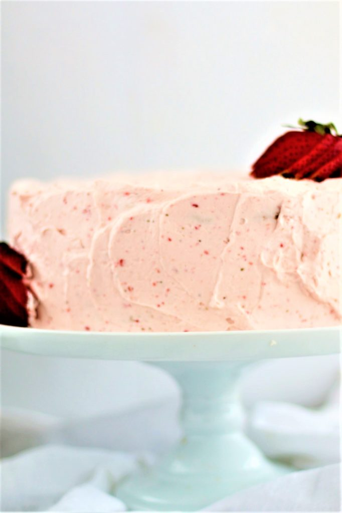 gluten free strawberry angel food cake on a white cake stand
