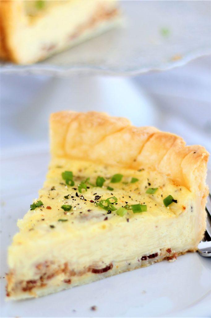 slice of gluten free quiche lorraine on white plate