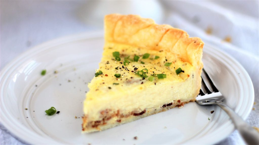slice of quiche on white plate with a sprinkling of chives