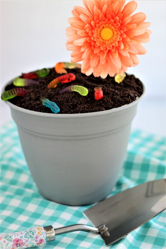 gluten free dirt cake in flower pot with gummy worms, flower, and trowel