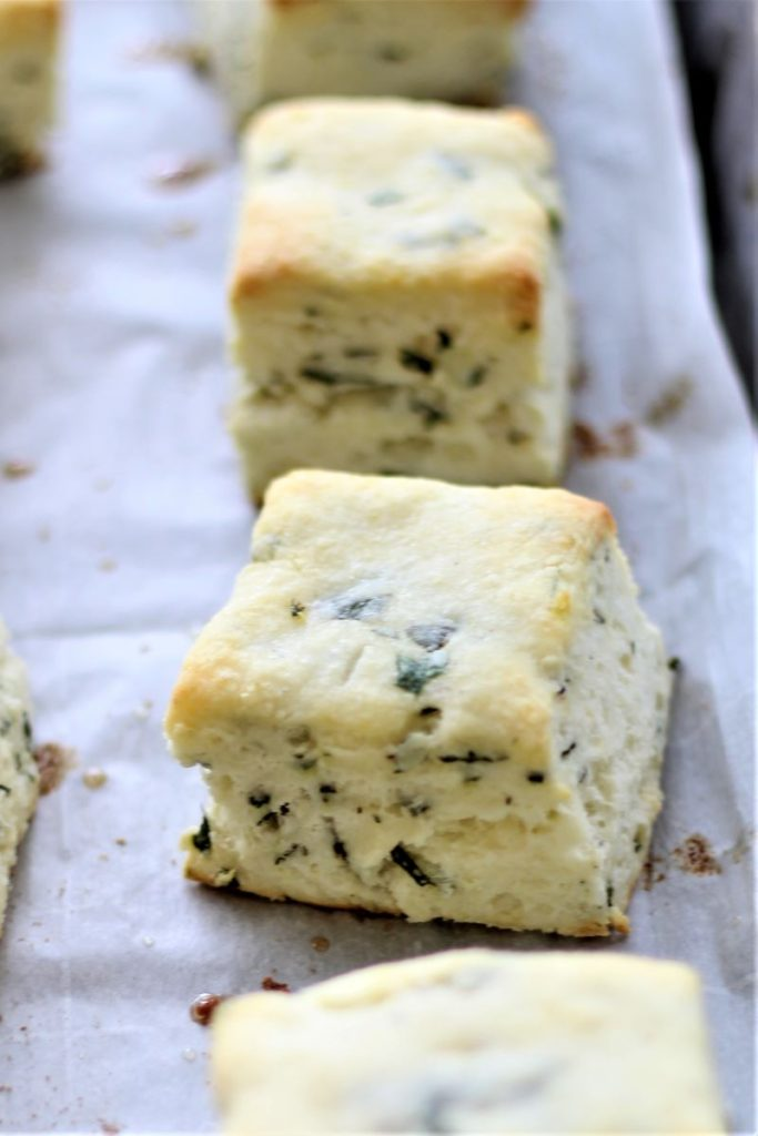 baked basil cream biscuits on parchment-lined sheet tray