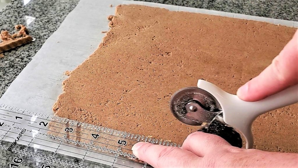 cutting the edges off the rectangle of cookie dough