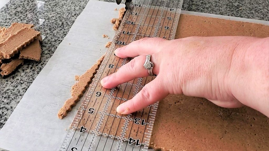 using ruler to cut off top edge of biscoff cookie dough