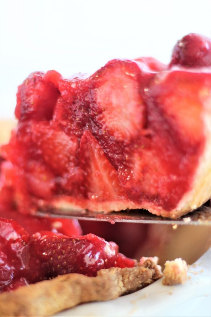 lifting slice of strawberry pie from whole pie