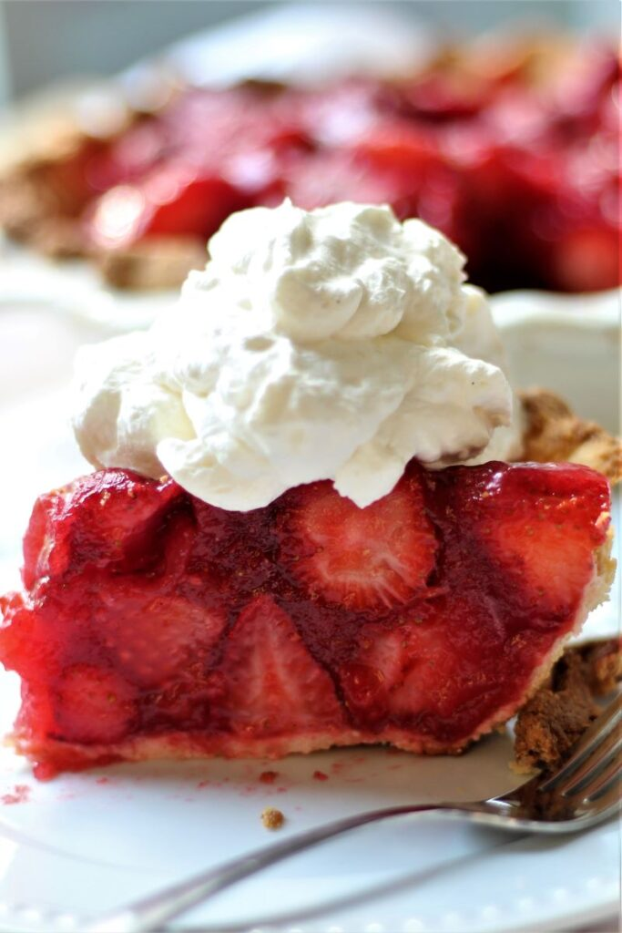 side view of slice of gluten free fresh strawberry pie with whipped cream on top