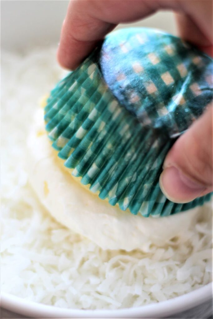 pressing cupcake into coconut