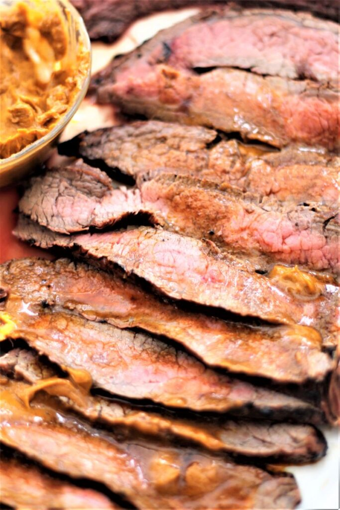 close up of chili butter flank steak with melted chili butter on slices