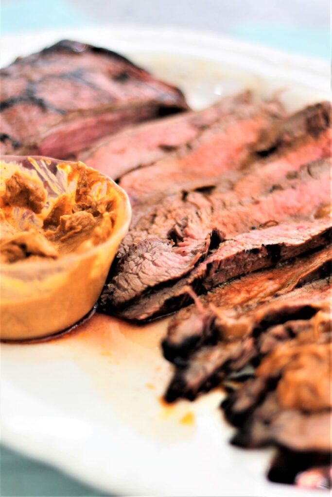 slices of chili flank steak with dollops of melted chili butter