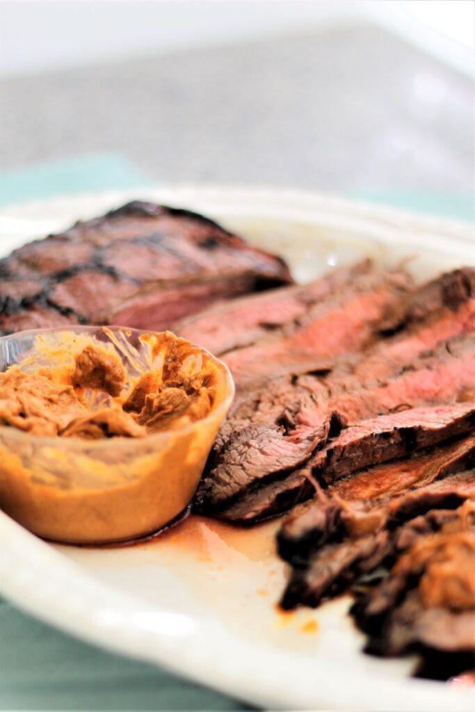 chili butter flank steak on white platter