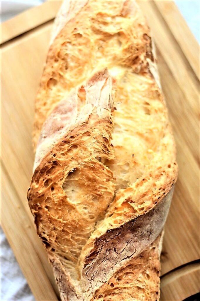 whole loaf of gf artisan bread on cutting board