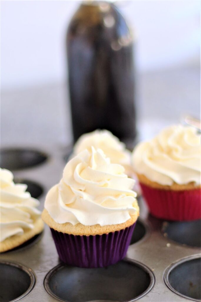 cupcakes sitting on top of muffin tin with bottle of vanilla in background
