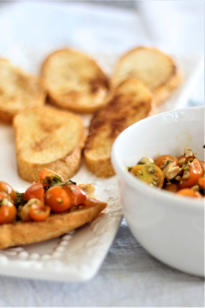 white bowl of marinated tomatoes next to platter of toasted crostini