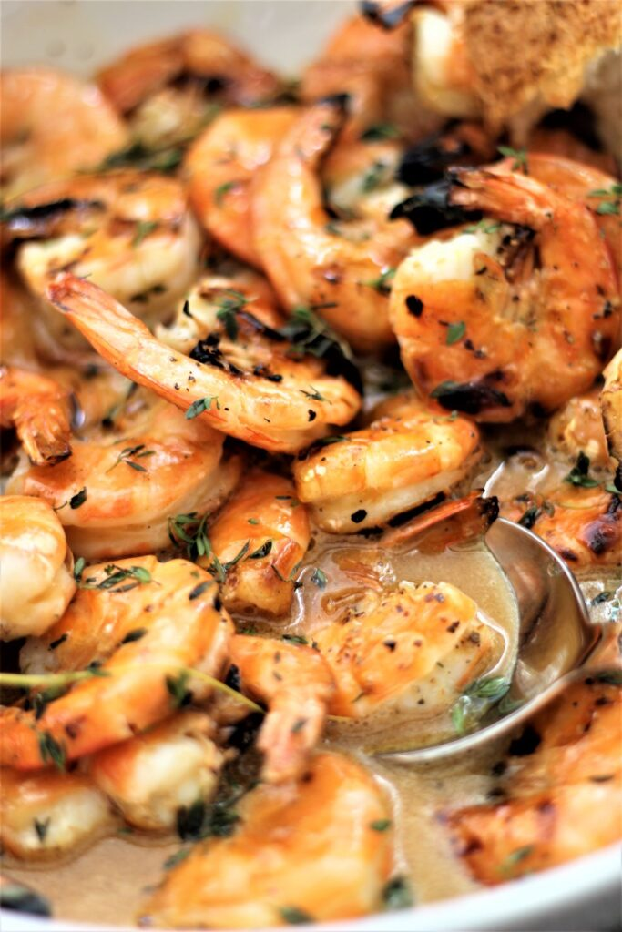 shrimp in large white bowl with metal spoon and torn bread