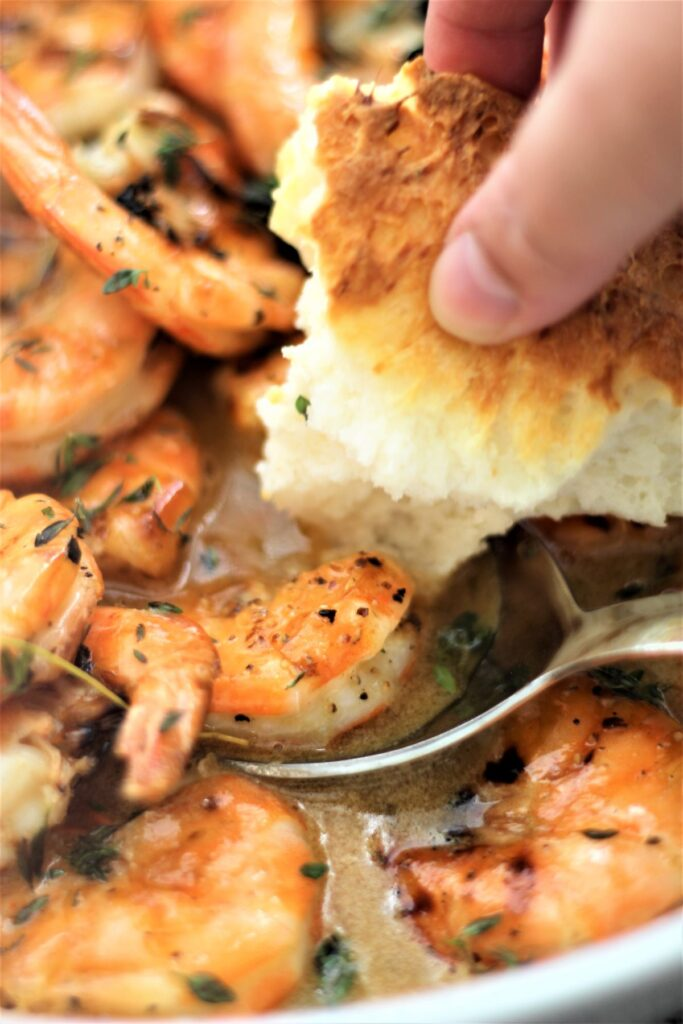 shrimp in a white bowl and dipping the bread into the sauce