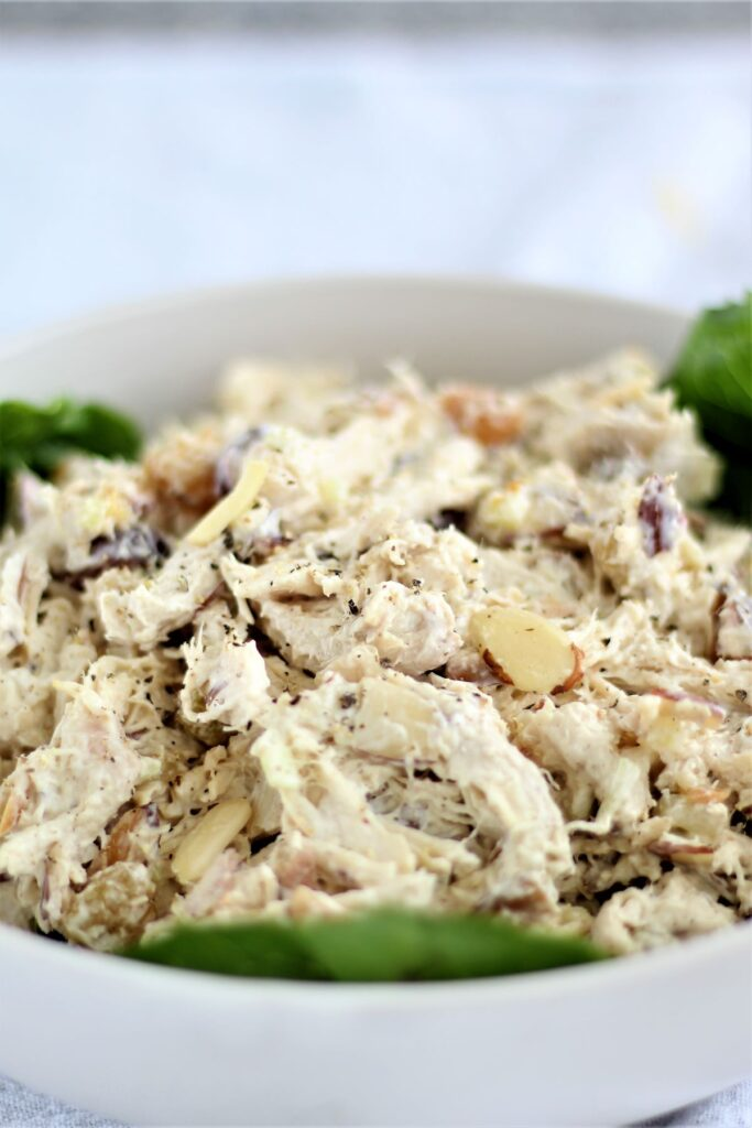 chicken salad in white bowl lined with lettuce leaves