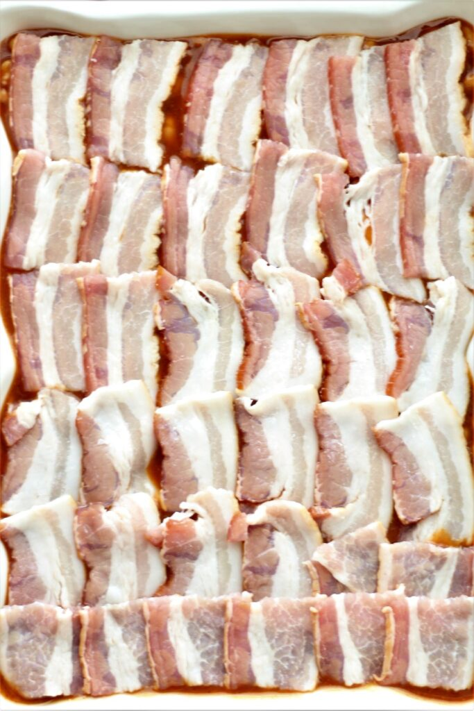 bacon pieces lined up in rows on top of baked beans