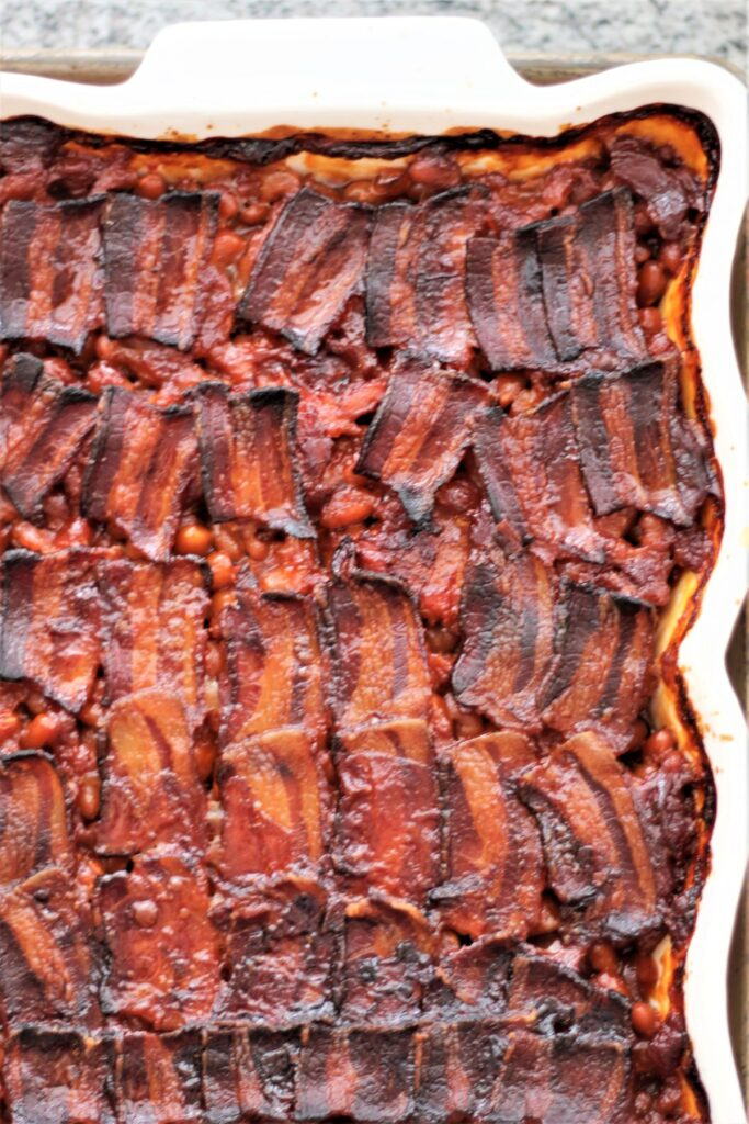 baked beans in white rectangular dish with caramelized bacon on top
