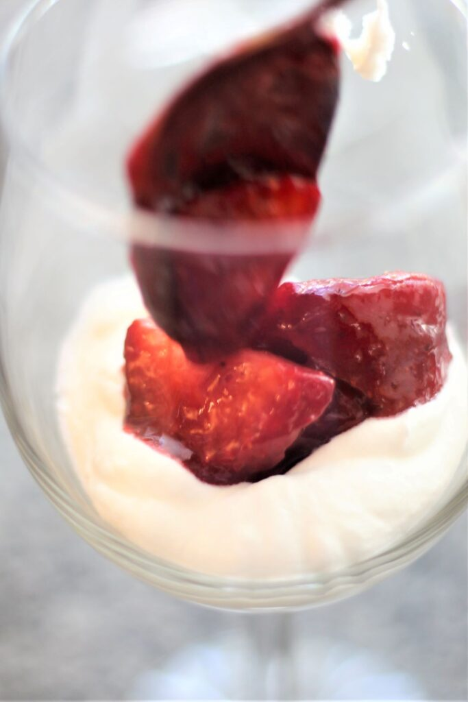 adding sauced strawberries on top of whipped cream in glass