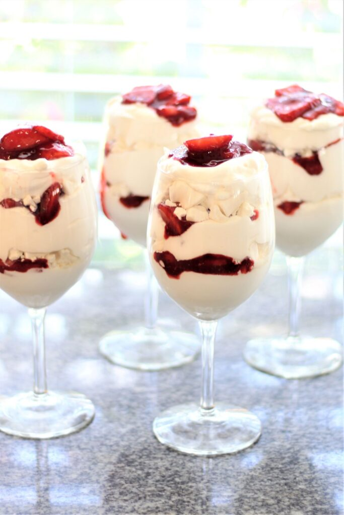 four wine glasses filled with eton mess