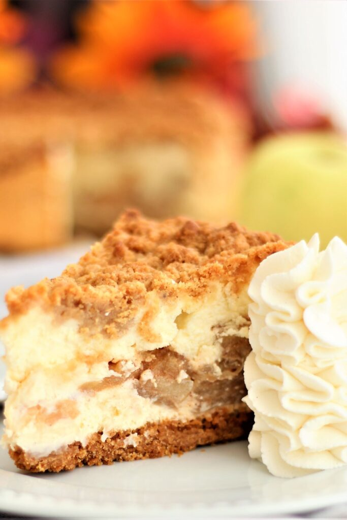 slice of gf dutch apple cheesecake with mound of piped whipped cream on white plate